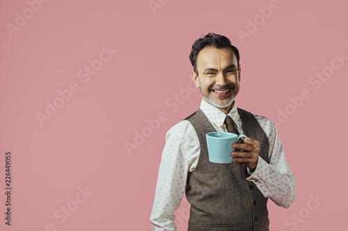 Leinwanddruck Bild Smiling mature man holding coffee mug, isolated on pink studio background