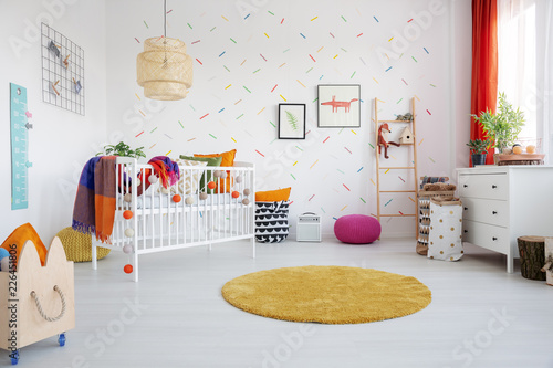 Leinwandbild Motiv Orange round rug and posters in colorful kid's room interior with cradle and wooden crate. Real photo