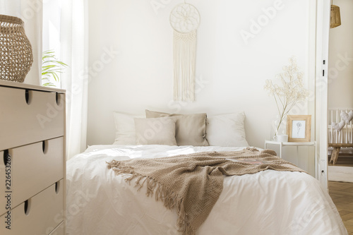 Blanket on white bed with pillows and wooden cabinet in minimal natural bedroom interior. Real photo