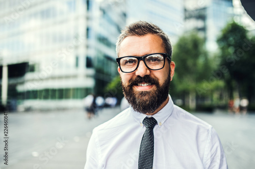 Poster A close-up portrait of hipster businessman with glasses in the city.