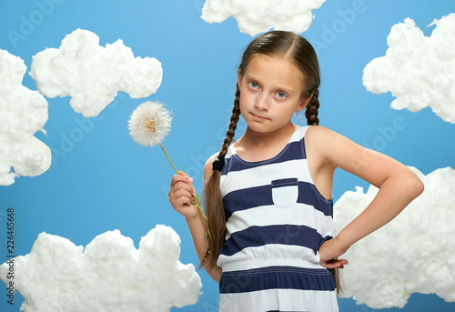 girl has a big dandelion in her hands, dressed in striped dress, posing on a blue background with cotton clouds, the concept of summer, holiday and happiness - 226465668