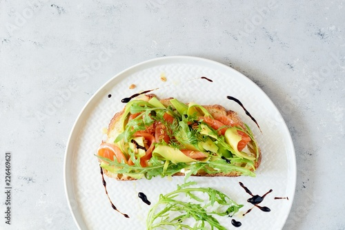 Brusctta with avocado, salmon, fresh leaves of arugula and balsamic. Breakfast with fresh organic greens, snacks, gravlax - 226469621