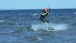 SLOW MOTION: A male kite surfer rolls on the board on the surface of the water. The kiter takes the jump.