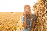 Image of stylish woman 20s standing near big haystack in golden field, and smoking cigarette during sunny day - 226485654