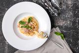 паста с ветчиной и базиликом на кухонном столе - 226489885