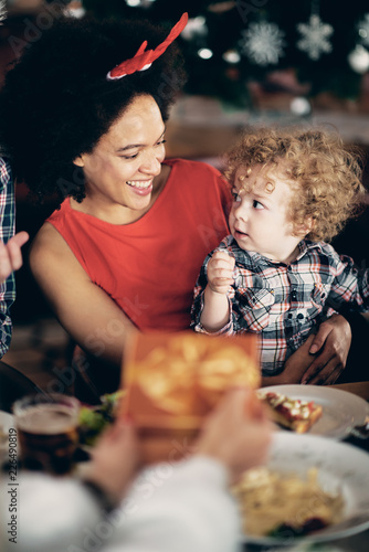 Foto Murales Mixed race woman holding toddler while sitting at table. Christmas eve concept