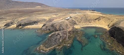 Vista aerea delle coste frastagliate e delle spiagge di Lanzarote, Spagna, Canarie. Strade e sentieri sterrati. Bagnanti in spiaggia. Spiaggia di Papagayo - 226491696