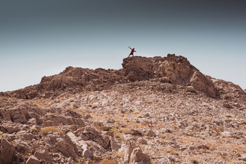 young boy have fun in a rocky desert - freedom and adventure lifestyle and sport concepts