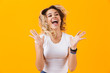 Quadro Photo of young woman in basic clothing screaming and expressing happiness, isolated over yellow background