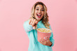 Leinwandbild Motiv Image of cheerful european woman 20s holding bucket with popcorn and looking at camera, isolated over pink background
