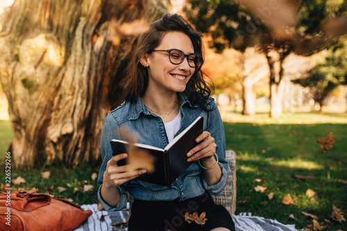 Smiling woman sitting at park with book and leaves falling aroun