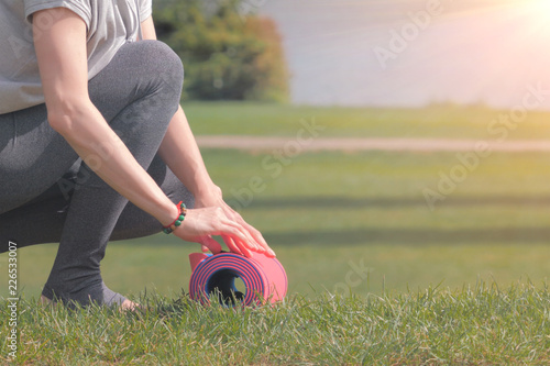 Woman going to practicing yoga, unrolling or rolling her yoga mat