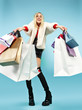 Leinwanddruck Bild - Full length portrait of a beautiful smiling funny blonde woman walking with colorful shopping bags isolated over blue studio background. The lifestyle, fashion, sale, shopaholic concept