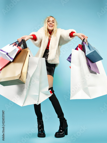 Leinwanddruck Bild Full length portrait of a beautiful smiling funny blonde woman walking with colorful shopping bags isolated over blue studio background. The lifestyle, fashion, sale, shopaholic concept