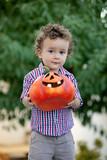 Funny baby holding a big pumpkin - 226540042