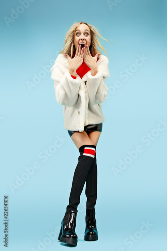 Full-length portrait of young elegant blonde funny woman at studio. Female fashion and shopping concept. The lifestyle, sale, shopaholic concepts