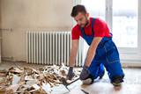 Handyman during work of removing old flooring - 226548429