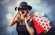 Leinwandbild Motiv Portrait of a young style girl in black dress and hat with shopping bags and binoculars on gray background with bokeh