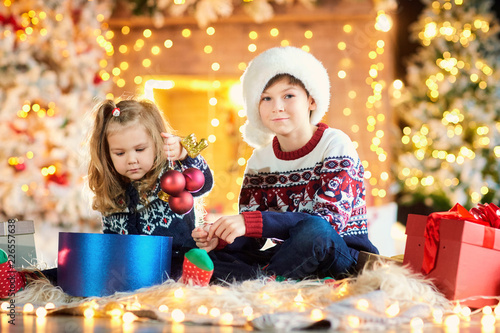 Foto Murales Children in a santa hat play playing on the floor indoors on Christmas Day.