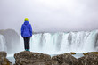 A beautiful young woman is standing against the backdrop of a beautiful waterfall. Iceland - 226558032