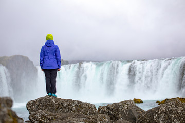 A beautiful young woman is standing against the backdrop of a beautiful waterfall. Iceland