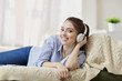 Girl in headphones smiling listening to music sitting in the room.