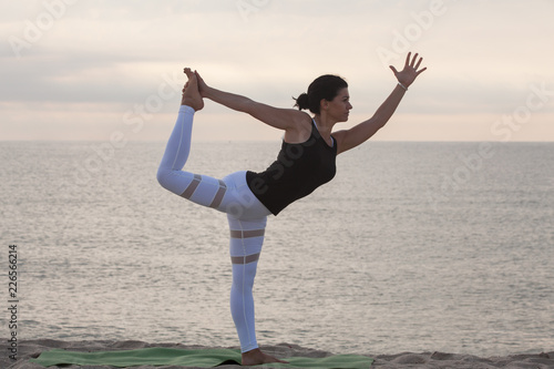 Fototapeta Woman practicing yoga on the beach. King Dancer Pose, Natarajasana. Outdoors sports. Healthy living.