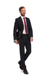 young businessman holding briefcase steps and looks to side © Viorel Sima