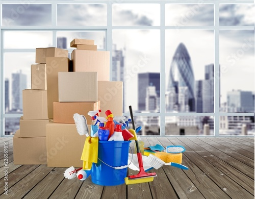 Foto Murales Cleaning supplies with moving boxes on background