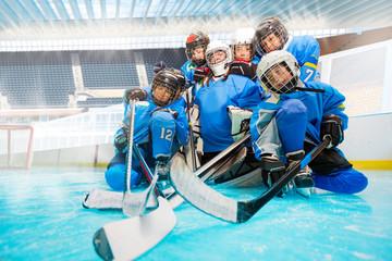 Junior hockey team with goalie on ice rink