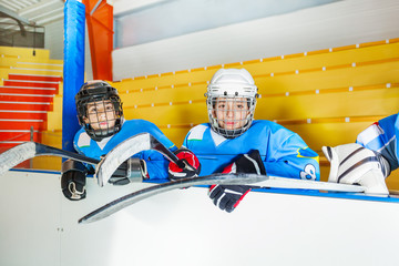 Young hockey players sitting on bench at stadium