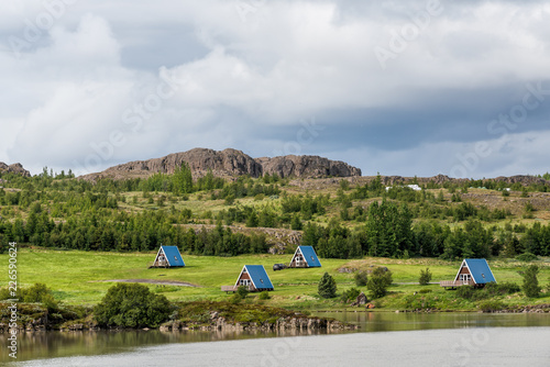Leinwanddruck Bild Egilsstadir, Iceland Cottages or cabins by Fellabaer city and river on ring road with traditional hut architecture, blue roofs for camping