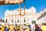 Macro closeup of wooden handmade Italian cross Catholic Assisi rosary with bokeh background of Vatican church St Peter's Square Basilica during mass on sunny summer day