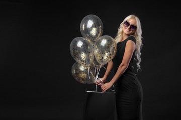 Brightfull expressions of happy emotions of amazing girl celebrating party on black background. Luxury black dresses, smiling, golden tinsels, big balloon, long curly hair, stylish look © shcherban