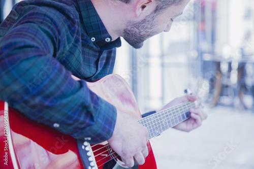Caucasian man playing the guitar outdoors. Music, art, creativity concept.