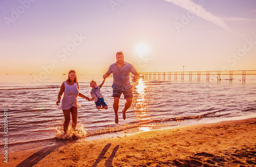 happy family jump on the shore on sunset light
