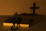 The bible and cross rosary beads on the wooden background with light lantern for blessed Sunday or Christianity .