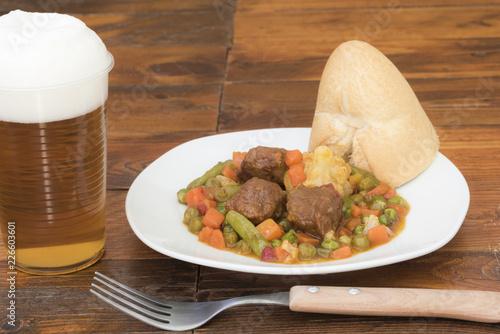Foto Murales Plato de albóndigas con verduras y un vaso de cerveza.