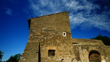 Ancient stone farmhouse in an Italian countryside, with blue sky and clouds