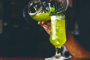 Barman pooring cocktail.