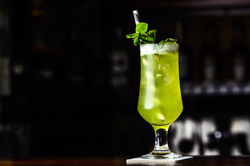 Green cocktail with mint and lemon on the bar.