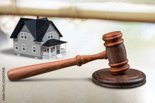 Wooden judge gavel and toy house on