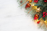 Fir branch with Christmas decorations and glowing garland on old wooden shabby background with empty space for text. Top view. - 226694664