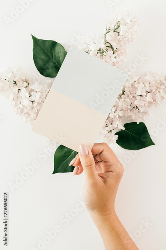 Top view female hand holding blank card flowers white Wedding background Flat lay - 226696022