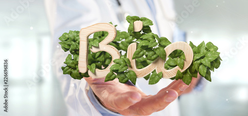 Doctor holding Wooden logo bio with leaves around 3d rendering - 226696836