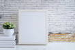 white wooden frame, books and houseplant on white table with old brick wall and copy space.