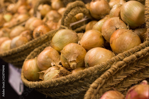 bulb onion in wicker baskets on market counter
