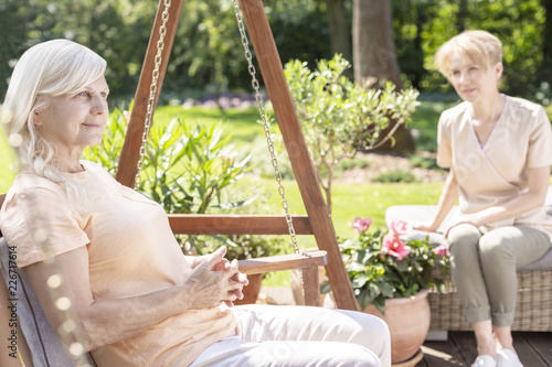 Wall mural Smiling senior woman on hanging chair in the garden with caregiver