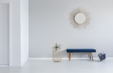 Gold mirror on the wall above blue bench in minimal empty entrance hall interior with plant. Real photo - 226718471