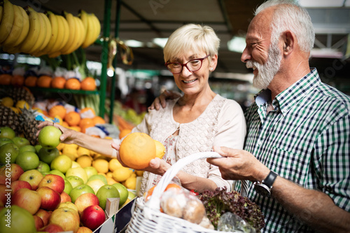 Leinwanddruck Bild Only the best fruits and vegetables. Beautiful senior couple buying fresh food on market